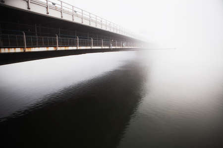 Bridge side view with reflection in the water  . Donaubrucke in the foggy morning Stok Fotoğraf - 154809743