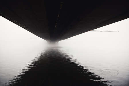 Fog under the bridge . Haze over Danube water . Bridge underside with reflection in the water
