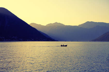 Calm morning on the bay with dawn . Fishing boat on the lagoon surrounded by mountains . Spectacular nature of Kotor Bay Stok Fotoğraf