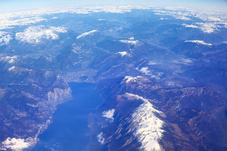 Flying above earth with mountains with snowy peaks