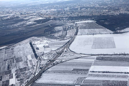 Flying over the snowy hills . Winter aerial view of Chisinau city edge