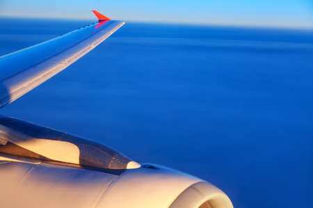 Airplane flying over the sea . View of wing and engine from the airliner window