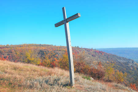 Autumn scenery with wooden cross on the hill 스톡 콘텐츠