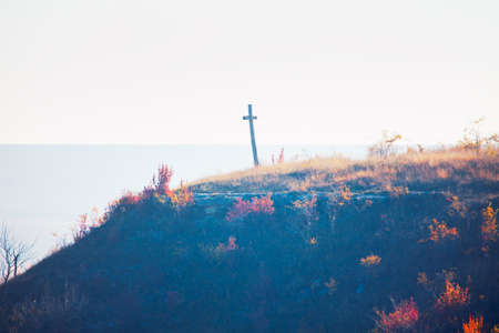 Wooden cross on the autumn hill . Christianity symbol on the top 스톡 콘텐츠