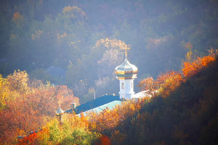 Orthodox church with golden dome situated on the downhill . Autumn scenery with church