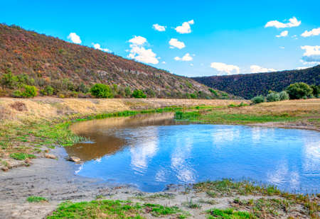 landscape with hills around pond 스톡 콘텐츠