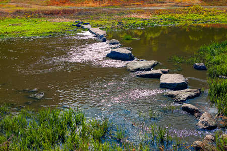 Stones in flowing water for crossing the river