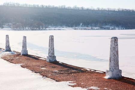 Pillars at the frozen lake shore