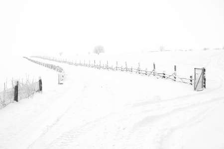 Rustic fence along snowy road . Country road covered by snow in winter