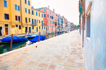 Street and water canal with boats on Venice . Sidewalk in Venezia