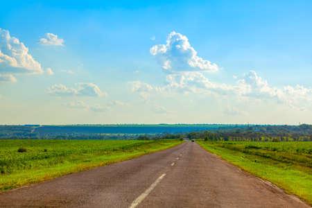 Asphalt road through the green fields Stok Fotoğraf