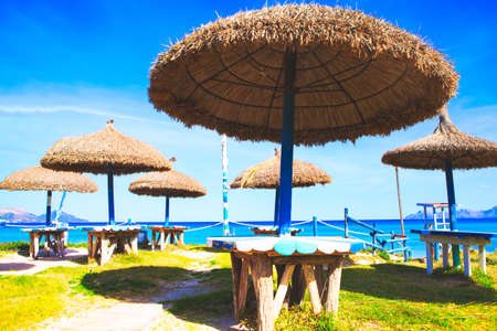 Exotic beach umbrellas and tables . Summer tropical terrace