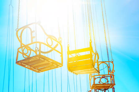 Swing on chains in the sunlight . Nobody at the amusement park