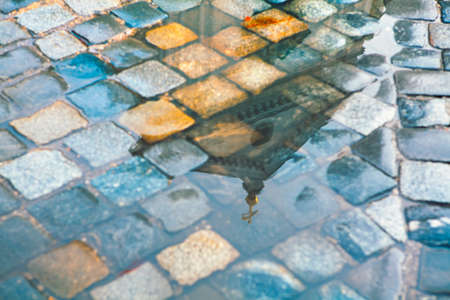 Reflection of church in the rain pool on the cobblestone