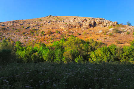 Rocky hill with green meadow . Natural hill scenery
