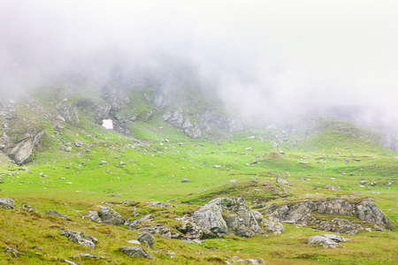 Majestic green and rocky mountain in fog
