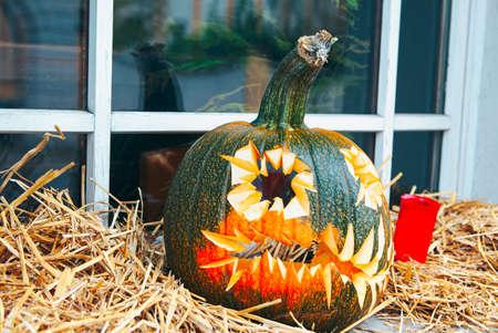 Jack-o-lantern on hay . Carved squash for halloween Stok Fotoğraf