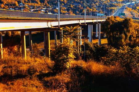 Beam bridge with highway scenery . Autumn landscape with bridge