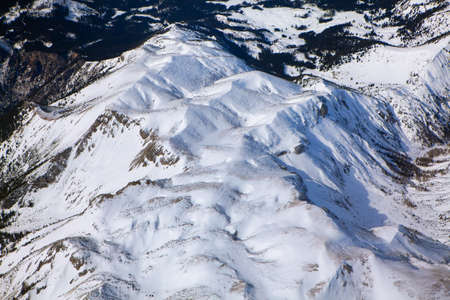 Above the snowy mountains . Aerial View of Frozen Peaks