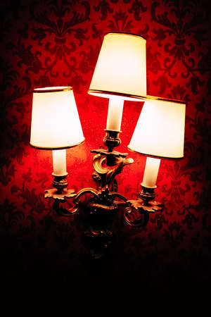 Delux bell lampshade on the wall in dim light . Lamps at the illuminated red wall Stockfoto