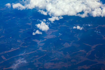 Flying above blue land and white clouds Stockfoto