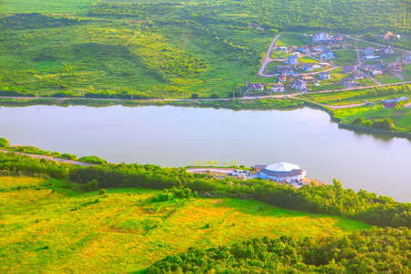 Village situated on the lakeside . Aerial view of spring green meadow and lake