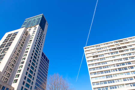 White buildings against blue sky . Airplane leaves track over the skyscrapers