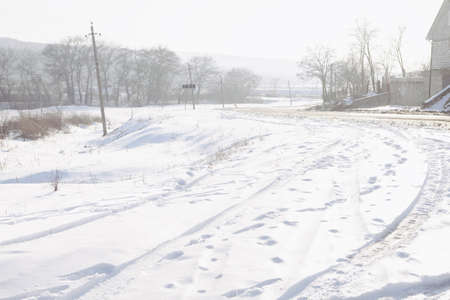 Country road covered by snow . Car prints on the snowy road