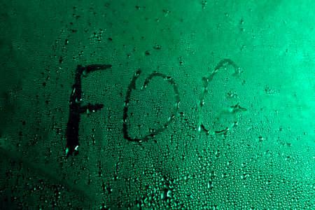 The word fog written on the wet glass