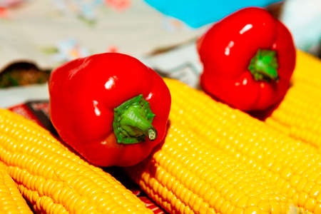Sweet peppers and corn . Bell pepper and maize . Red and yellow vegetables