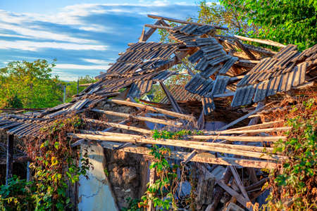 Destroyed country house with broken roof Stockfoto