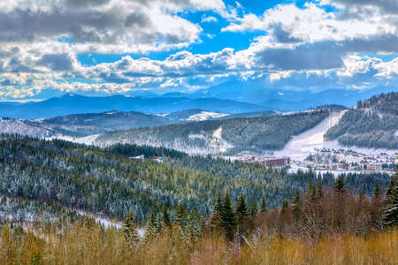 Ski resort in the mountains . Winter landscape with forest and mountains