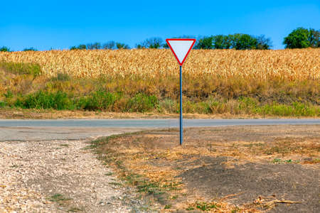 Country road and agricultural field . Road sign give way Stockfoto