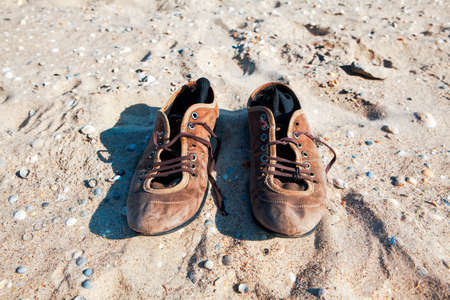 Old leather shoes on the beach . Socks inside shoes