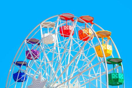 Ferris Wheel with colorful cabins . Amusement park