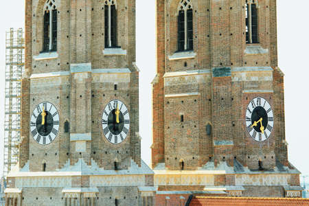 Two towers top of Gothic church . Frauenkirche cathedral in Munich Germany . Tower clock