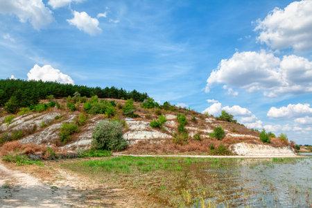 Limestone hill at the riverside . Coastal rocks scenery Reklamní fotografie