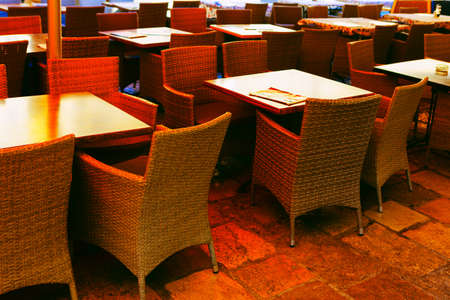 Empty chairs and tables of restaurant . No people in the restaurant . Cozy place for dinner