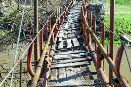 Rickety bridge for pedestrian passing across the river . Trekking with adventure