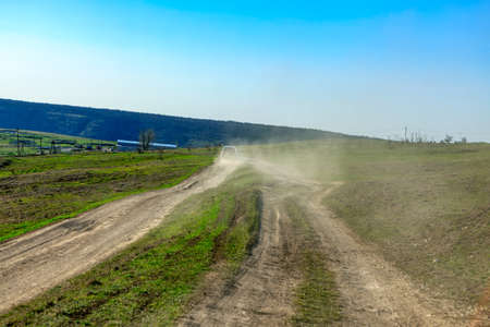 Car on country road raises dust . Rural journey Imagens
