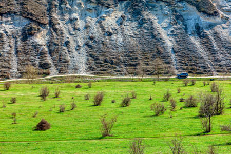 Nature discovery by car . Driving along rocky cliffs . Green Meadow and Hill Imagens