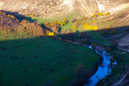Wide aerial panorama of a landscape with meadows on hills . Riverside valley aerial view