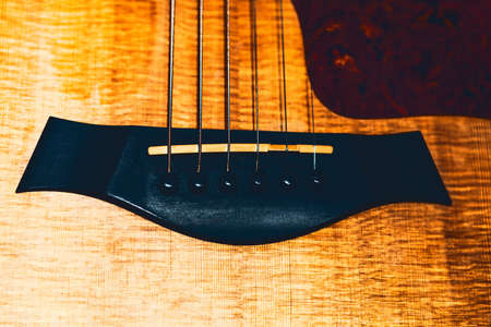 Wooden bridge of acoustic guitar with strings and pins