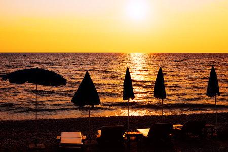 Beach umbrellas during sunset . Paradise seaside in the twilight . Summertime vacation destination