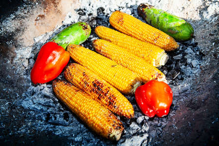 Cooked vegetables on the fire . Corns, peppers and zucchini . picnic with healthy eating