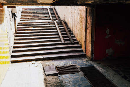 Destroyed underground passage in the city . Broken stone staircase . Need of repair