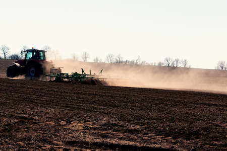 Tractor Plowing Agricultural Field in the Spring . Dust over the agricultural field Stok Fotoğraf