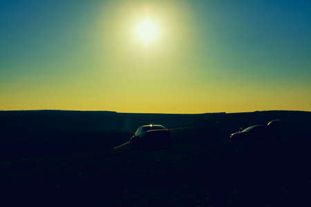 Silhouette of cars on the hill . Sundown over the country