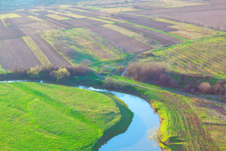 Aerial view of gardens and flowing river . Agricultural fields view from above . Spring nature panorama