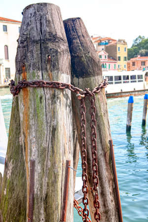 Old Wooden Berth Pillars for Boats . Place for parking gondolas in Venice . Rusty chains for moored boats